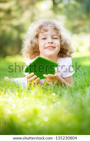 Child holding green grass house in hands. Ecology concept - stock photo