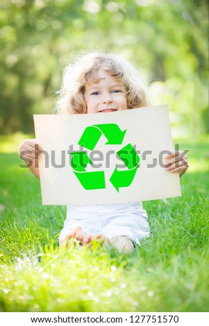 Child holding paper with recycle symbol against green spring background. Ecology concept - stock photo