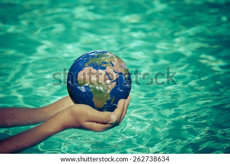 Child holding planet in hands against blue water background. Earth day holiday concept. Elements of this image furnished by NASA - stock photo