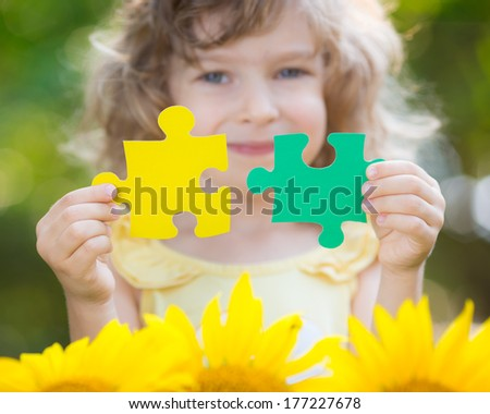 Child holding puzzles in hands against spring green background. Teamwork and partnership concept - stock photo