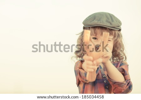 Child holding slingshot in hands against summer sky background. Retro style - stock photo