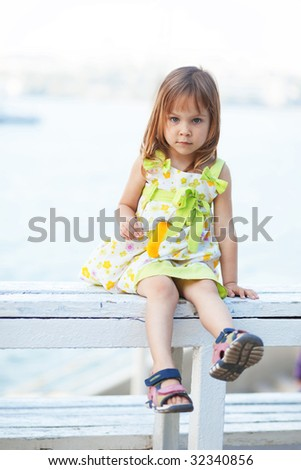 Child holding small toy posing outdoor - stock photo