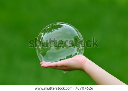 Child holding soap bubble with house reflection - stock photo