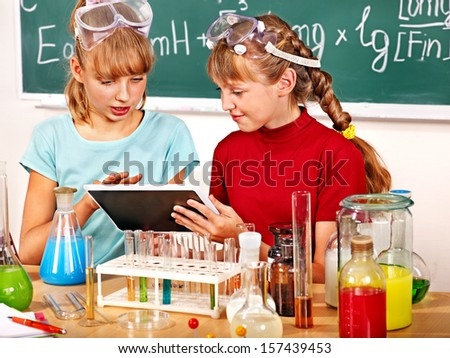 Child holding tablet pc in chemistry class.