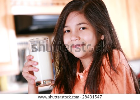 Child holding tall glass of delicious milk