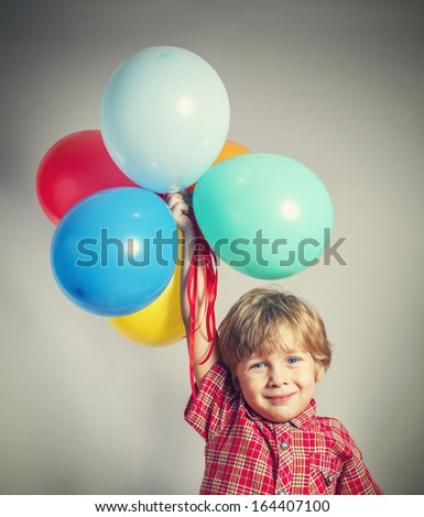Child holding the bunch of balloons - stock photo