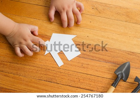 child holding tiny wooden house - stock photo
