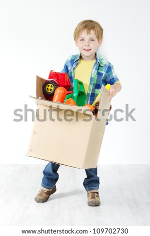 Child holding toys packed in cardboard box. Moving and growing concept - stock photo