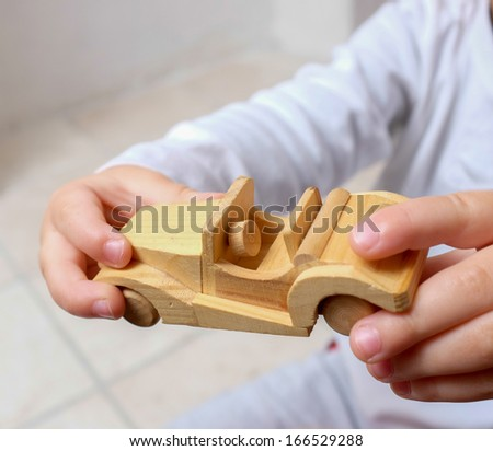 Child holding wooden car - stock photo