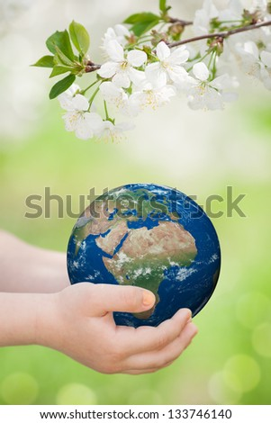 Child holding world in hands against green spring background. Earth day concept. Elements of this image furnished by NASA - stock photo