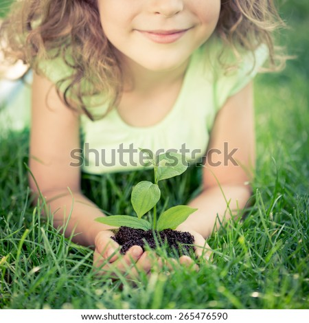 Child holding young green plant in hands. Kid lying on grass in spring park. Earth day concept - stock photo