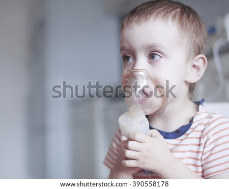 child holds a mask vapor inhaler. treatment of asthma. breathing through a steam nebulizer. concept of inhalation therapy apparatus. copy space for your text - stock photo