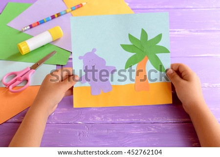 Child holds a paper card with a Hippo and a palm tree. Colored paper sheets, scissors, pencil, glue stick lilac on wooden background. Cute and easy hand craft for preschoolers  - stock photo