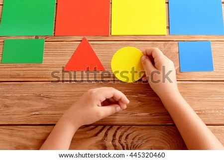 Child holds a yellow cardboard circle in hands and puts on a corresponding color card. Child learns colors. Set of colored cards for kids of preschool age. Idea for learning in kindergarten, at home - stock photo