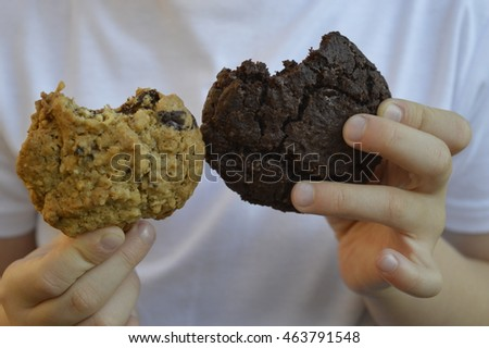 Child holds in hand two bitten cookies: oatmeal and chocolate