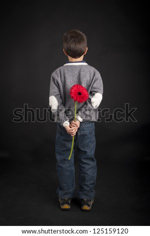 Child holds red flower behind his back. Black background. - stock photo