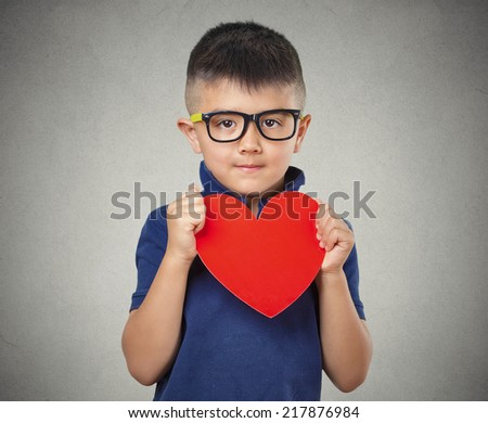 Child holds red heart, isolated grey wall background. Positive human emotions, feelings, attitude, life perception, face expressions. Compassion concept - stock photo