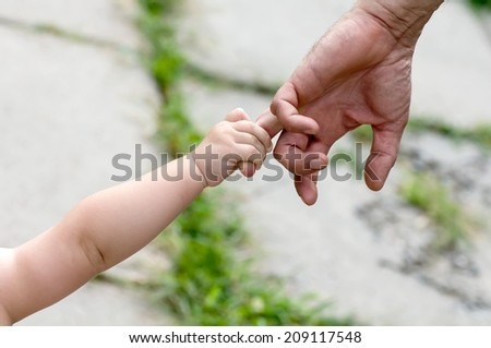 child holds the finger of a hand of the father - stock photo