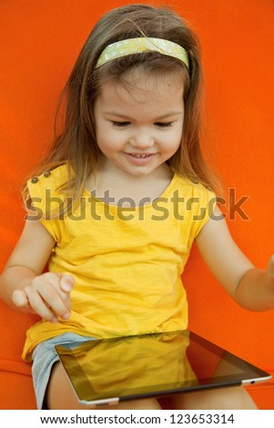 Child holds the plate on an orange background - stock photo