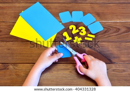 Child holds the scissors and cuts paper card. Paper sheets and numbers on a brown wooden background. Education concept - stock photo