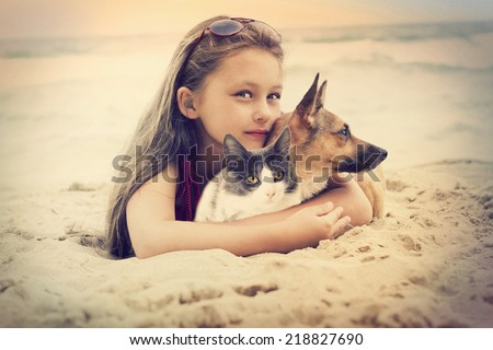 child hugging a cat and dog - stock photo