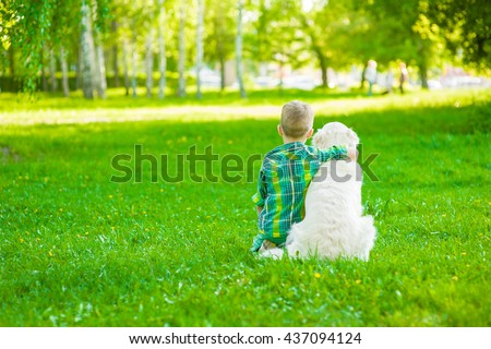 Child hugging golden retriever, sitting with his back to the camera - stock photo