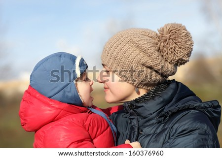 Child hugging mother at the park in autumn - stock photo