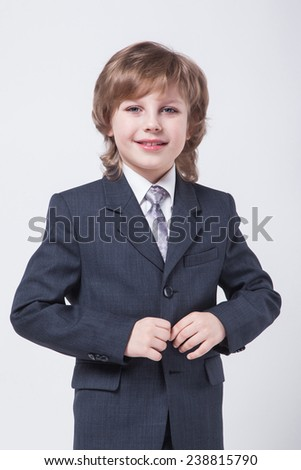 child in a classic suit straightens his jacket, the image of a successful ambitious businessman on a white background with a smile - stock photo