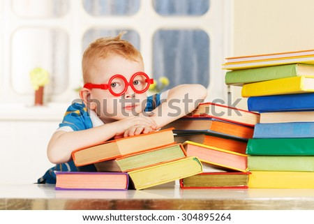 Child in a classroom with a books.  - stock photo