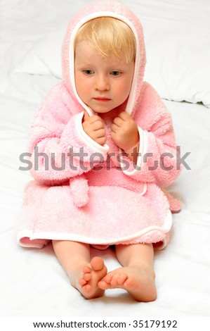 Child in a dressing gown sits on a bed - stock photo