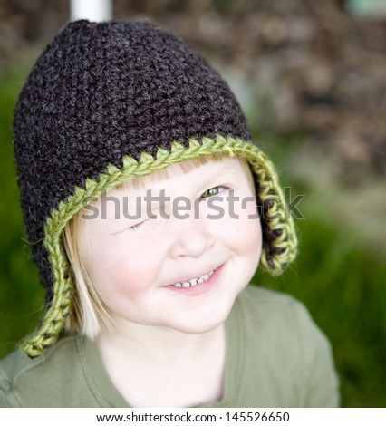 Child in a fun hand-knit hat, winking - stock photo