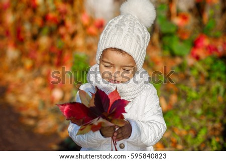Child in autumn orange leaves playing