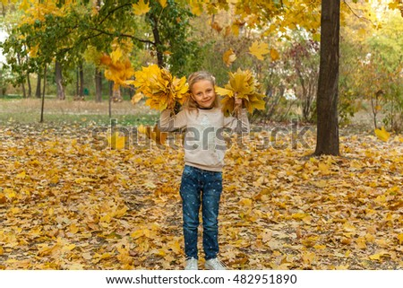 Child in autumn park.Autumn portrait of a girl in sweater and jeans in autumn park among fallen yellow leaves.