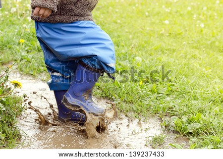 Child in boots jumping in muddy puddle after rain.