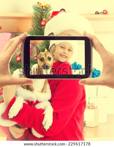 child in Christmas clothes holding his dog and posing for a photograph - stock photo