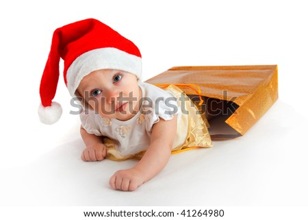 child in christmas hat crawl-out from the bag with presents