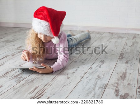 Child in christmas hat with tablet lying on floor. Girl playing computer - stock photo