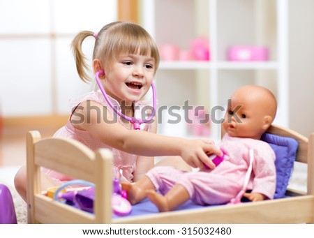 Child in kindergarten. Kid in nursery school. Little girl playing doctor with doll - stock photo