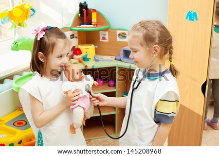 Child in kindergarten. Kids in nursery school. Girl playing with doll at infant school - stock photo