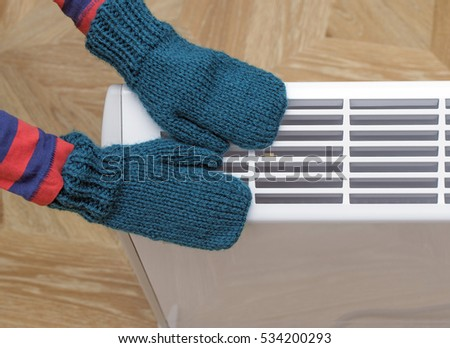 Child in knitted mittens touching heating electric radiator.