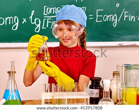 Child in mask holding flask in chemist class. Child is chemist researcher in chemistry class. - stock photo