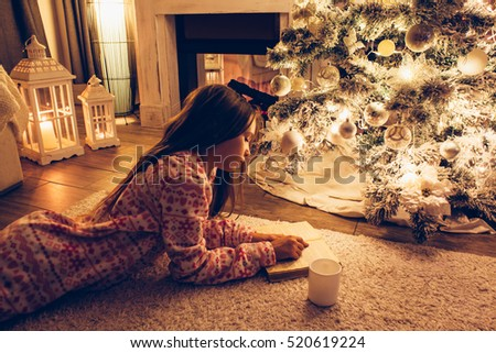 Child in pajama reading book and chilling on a floor by the Christmas tree in decorated room some december night, winter weekends, cozy scene
