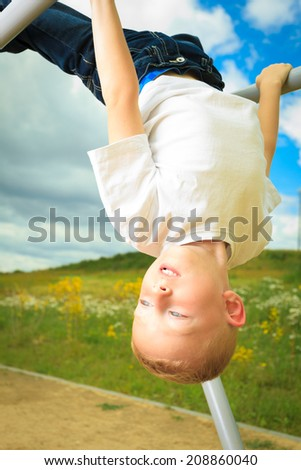 Child in playground in action boy playing on leisure equipment. Kid hanging upside down on monkey bars - stock photo