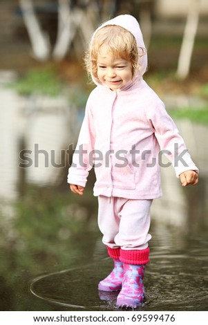 Child in puddle after summer rain