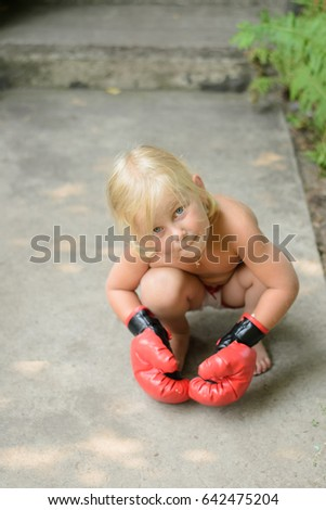 Child in red leather boxing gloves