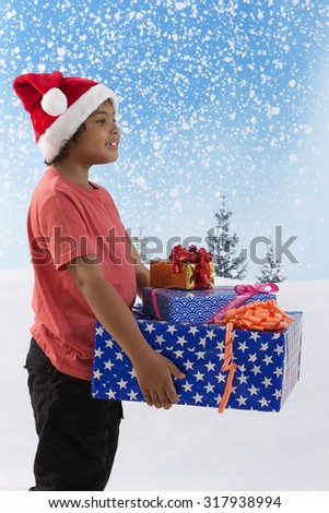 Child in red shirt and Santa hat holding   gifts - stock photo
