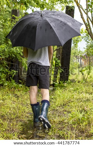 Child in rubber boots goes on a footpath to the wicket through a puddle in the rain under a black an umbrella on a background green - stock photo