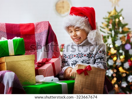 child in Santa hat looking at Christmas gifts - stock photo