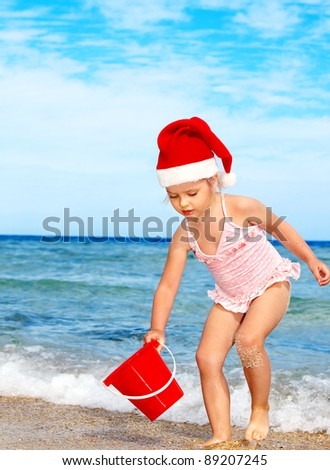 Child in santa hat playing on  beach. Summer New Year. - stock photo