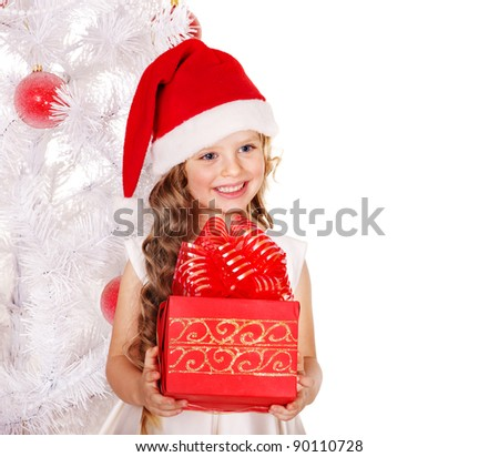 Child in Santa hat with gift box near white Christmas tree. Isolated. - stock photo